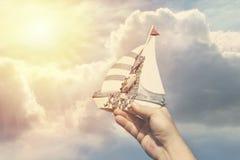 手工制造船在反对云彩背景的一只人` s手上作为旅行和梦想的标志 免版税库存照片