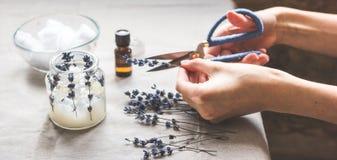 手工制造蜡烛用在纺织品背景的淡紫色 免版税库存照片