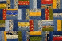 手工制造补缀品由蓝色牛仔布制成的样式,五颜六色的补缀品和鞋带磁带 免版税库存照片