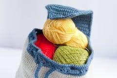 手工制造被编织的背包和毛线五颜六色的缠结  库存照片