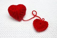 手工制造钩针编织心脏和红色毛线球象心脏在白色钩针编织背景 红色心脏由毛纱制成 浪漫克里斯 图库摄影