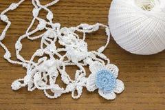 手工制造钩针编织白色链子和一朵蓝色花 讲故事钩针编织的球或编织在木桌上 自创项链 免版税图库摄影