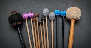 手工制造鼓和撞击声乐队自然山胡桃木棍子看法的片段在深灰的 免版税库存照片
