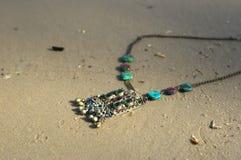 手工制造 在沙子的项链在unny天 库存照片