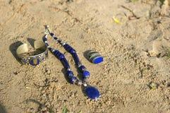 手工制造 项链圆环和镯子在沙子在unny天 免版税库存图片