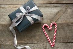 手工制造chistmas从黑包装纸、银色丝带和棒棒糖提出在心脏形状木表面上 的顶视图 免版税库存图片