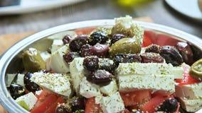 手工增加调味料特写镜头到希腊菜沙拉 素食烹调 健康的食物 影视素材