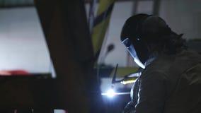 手工氩弧焊在黑暗的工厂,有面具的工作者技术员 慢的行动 影视素材