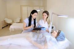 手工眼眉纹身花刺妇女大师与女性assistan谈话 库存图片