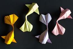 手工纸工艺origami金子koi和桃红色,在黑背景的绿色,紫罗兰色鲤鱼鱼 观看从上面,样式 免版税库存照片