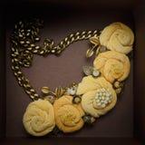 手工项链,包括五种桃色的颜色,由布料制成在一个棕色箱子在 免版税库存图片