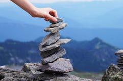 手平衡的岩石塔,山背景 图库摄影