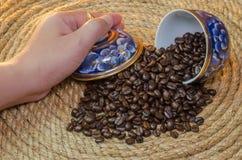 手开放咖啡豆在Benjarong黄麻绳索 免版税库存照片