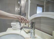 手开阔水域轻拍的特写镜头在卫生间里 免版税库存图片
