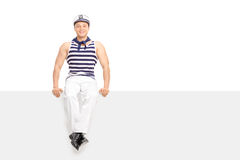 水手成套装备的人坐一个空白的广告牌 免版税库存照片