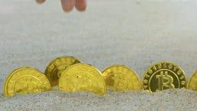 手手指拾起从行的Bitcoins在海滩宏指令的沙子 影视素材
