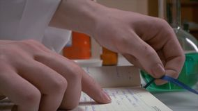 手打开和看某事在日志,笔记本 科学家文字的手在笔记本的,妇女` s手,做 免版税图库摄影