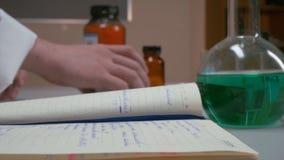 手打开和看某事在日志,笔记本 科学家文字的手在笔记本的,妇女` s手,做 库存图片