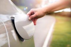 手打开汽车` s油盖帽加油 免版税库存图片