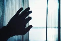 手打开窗口的,被定调子的蓝色薄纱 图库摄影