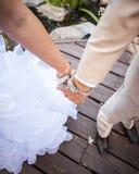 手扣上手铐在腕子的新娘和新郎一起武装和仅腿 图库摄影