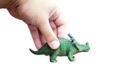 手抓住恐龙玩具 图库摄影