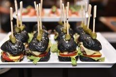 手抓食物套小黑汉堡包服务 图库摄影