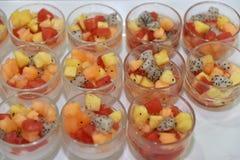 手抓食物点心:在玻璃碗的新鲜水果沙拉 免版税库存照片