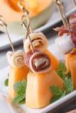 手抓食物:火腿和瓜在垂直的串 库存图片
