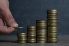 手投入了硬币对堆硬币,概念挽救金钱 免版税库存照片