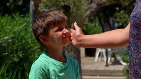 手抹上在男孩的面孔的防护奶油 影视素材