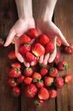 手拉手拿着草莓 库存图片