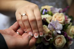 手拉手新娘新郎 在背景新娘婚礼花束的圆环 库存图片