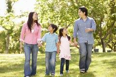 手拉手走在公园的亚洲家庭 免版税图库摄影