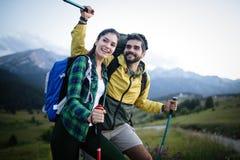 手拉手走在山的男人和妇女游人 免版税库存照片