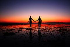 手拉手走在日落背景的夫妇惊人的剪影  免版税库存照片