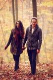 手拉手走在秋天的恋人 免版税库存照片