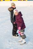 手拉手滑冰在溜冰场的男孩和女孩在冬天 免版税库存图片