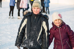 手拉手滑冰的兄弟和的姐妹 图库摄影