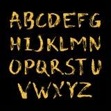 手拉的在书法刷子的闪烁金黄字母表 图库摄影