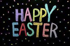 手拉的文本'复活节快乐'在黑板 库存图片