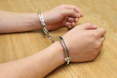 手拘捕与在木桌上的手铐 免版税库存图片