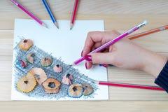 手拿着一支铅笔 在桌上的铅笔刀削片 库存照片