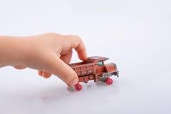 手拿着一辆红色玩具卡车 免版税库存照片
