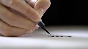 手拿着与一把刷子的一支笔在末端并且写道 股票录像