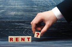 手拿着与感叹号的标志的一个立方体对词租 租赁和租赁租的一个房子,搜寻  库存照片