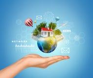 手拿着与房子、摩天大楼和树的地球 免版税库存照片