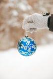 手拿着在冬天多雪的风景的被弄脏的背景的一个美丽的圣诞节球 库存照片