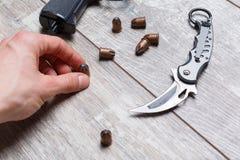手拿着在木地板上的一枚子弹 库存图片