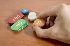 手拿着在木桌上的色的赌博娱乐场芯片 库存图片